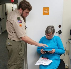 Eagle project leader, Jackson helping resident, Gail Jens